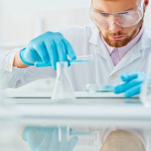 Chemist in protective eyeglasses and gloves working with liquid substances